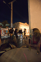 People dance in the streets as a band plays inside a bar in Santa Clara, Cuba.