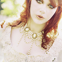 Close-up of a young woman with red hair wearing pearls and white victorian dress looking at camera