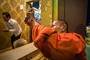 02 FEBRUARY 2013 - PHNOM PENH, CAMBODIA:   A Cambodian monk uses his cell phone to photograph into a small shrine where people were praying for former King Norodom Sihanouk in Phnom Penh. Much of Phnom Penh has been shut down to honor former King Norodom Sihanouk, who ruled Cambodia from independence in 1953 until he was overthrown by a military coup in 1970. Only bars, restaurants and hotels that cater to foreign tourists are supposed to be open. The only music being played publicly is classical Khmer music. Sihanouk died in Beijing, China, in October 2012 and will be cremated during a state funeral royal ceremony on Monday, Feb. 4.   PHOTO BY JACK KURTZ