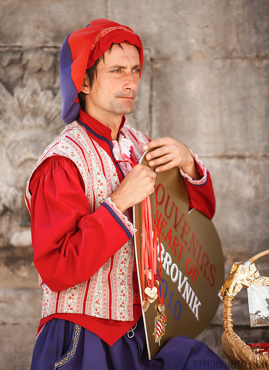 A man dressed in a traditional Croatian outfit selling souvenirs to tourists in Dubrovnik, Croatia.