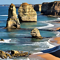 Sea Stacks at Twelve Apostles near Port Campbell on Great Ocean Road, Australia<br /> When approaching the Twelve Apostles Visitor Facility, you quickly discern from the parking lot full of tour buses and cars that you have arrived at Great Ocean Road's most famous location. Now walk through a tunnel beneath the highway and stand on the first viewing platform. You will be awed by this vison of limestone sea stacks. The tallest one reaches 111 feet. Notice the smaller mounds in the foreground. These are stumps of collapsed rock columns and all that remains of former Apostles.