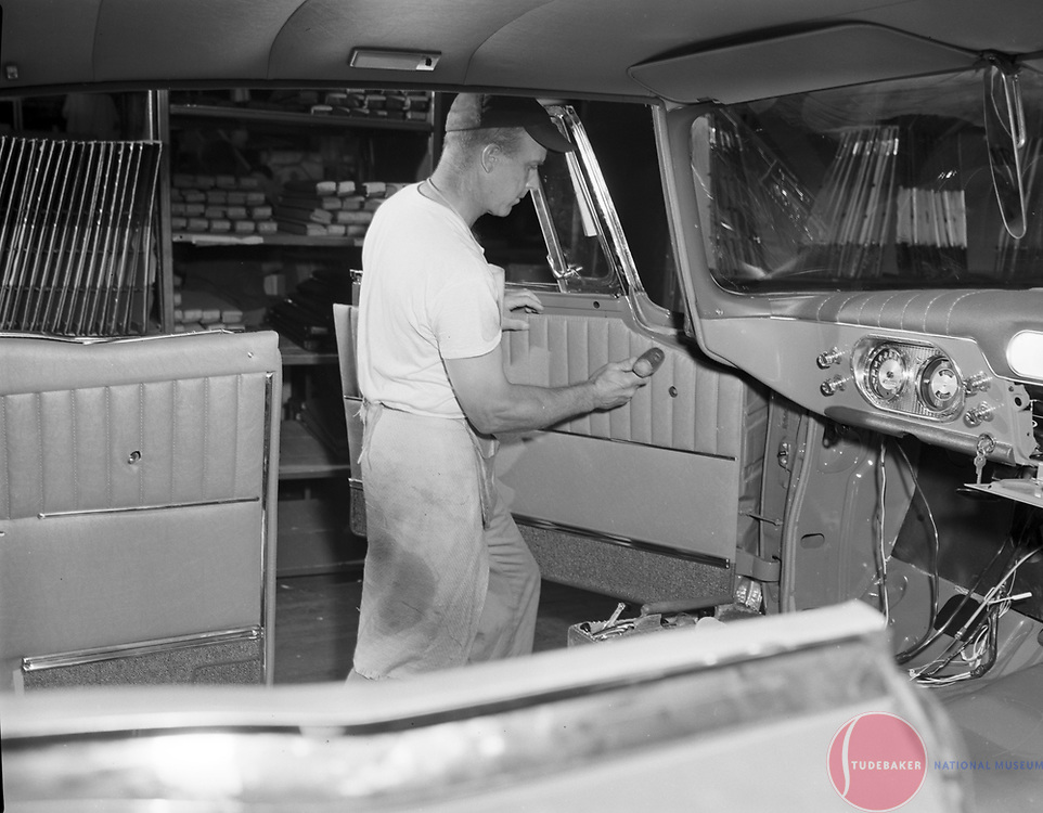 A Studebaker worker installs a door panel on a 1960 Studebaker Lark hardtop at the company's South Bend, Indiana, plant.