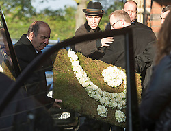© London News Pictures. 05/11/2014. Flowers in the shape of a music note being taken in to the service. . The funeral of Jack Bruce at Golders Green Crematorium in North London. Jack Bruce was the lead singer and bass player for British Rock band Creme, alongside Eric Clapton and Ginger Baker. Creme sold over 15 million albums worldwide and were widely considered to be the worlds first successful supergroup. Photo credit : Ben Cawthra/LNP