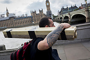 A workman with a tattoo on his arm carries a bundle of short wooden planks on his shoulder, about to cross Westminster Bridge towards the Houses of Parliament, on 12th September 2017, in London, England.