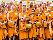 05 DECEMBER 2014 - BANGKOK, THAILAND:  Buddhist monks line up on Sanam Luang, the parade ground in front of the Grand Palace, for a Buddhist prayer service for Bhumibol Adulyadej, the King of Thailand. Thais marked the 87th birthday of the King Friday. The revered Monarch was scheduled to make a rare public appearance in the Grand Palace but cancelled at the last minute on the instructions of his doctors. He has been hospitalized in Siriraj Hospital, across the Chao Phraya River from the Palace, since early October.   PHOTO BY JACK KURTZ