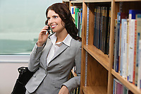 Woman talking on mobile phone in library