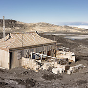 Cape Royds hut, this side was where the pony stable was located. supply cases, fodder and dog huts can be seen. The hill behind is the Adelie penguin colony. The yellow color on the hillside? That's not dirt.