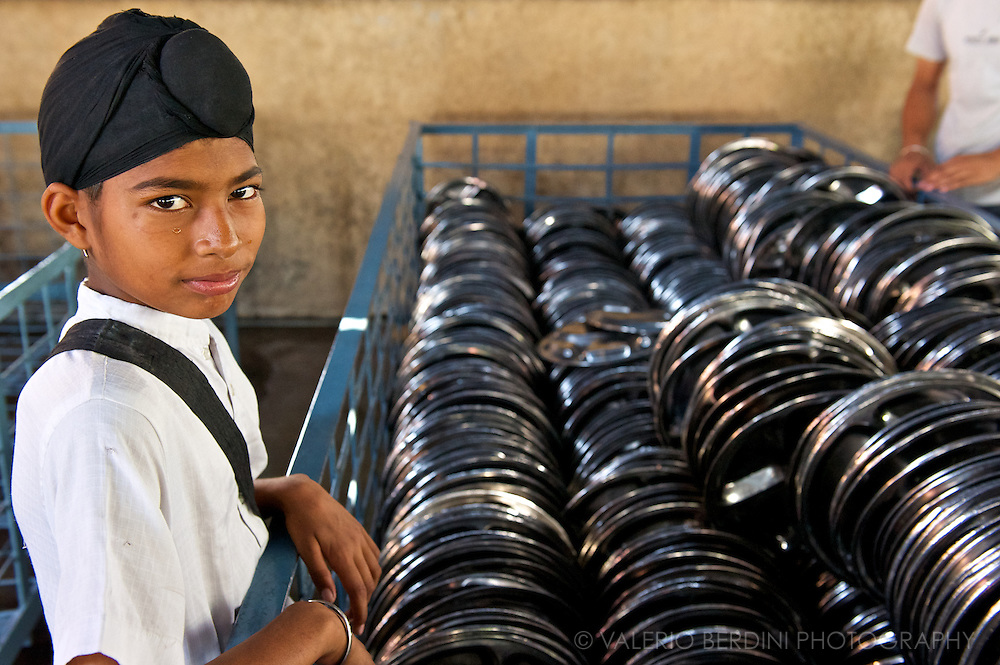 A young boy lines up all the clean plates, ready for another round. <br /> Using only metal dishware and very little cutlery in the Indian tradition of eating using hands there is a minimal turnover of broken items.