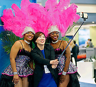 """Victoria Gong of South Korea uses a selfie stick as she poses with       during the Cruise Shipping Miami conference  annual """"State of the Industry"""" address from cruise line executives on Tuesday, March 17, 2015."""