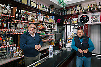 TARANTO, ITALY - 22 FEBRUARY 2018: (L-R) Ignazio D'Andria, owner of the Mini Bar, and Giulio Vecchione (47), an ILVA contractor who provides transportation services, are seen here at the Mini Bar in Tamburi, the working-class district adjacent the ILVA steel mill in Taranto, Italy, on February 22nd 2018.<br /> <br /> Taranto, a  formerly lovely town on the Ionian Sea has for the last several decades been dominated by the ILVA steel mill, the largest steel plant in Europe. It was built by the government in the 1960s as a means of delivering jobs to the economically depressed south, but has been implicated for a cancer as dioxin and mercury have seeped into local groundwater, tainting the food supply, while poisoning the bay and its once-lucrative mussels.