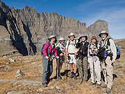 "A hiking group enjoys Piegan Pass and Mount Gould (far right), in Glacier National Park, Montana, USA. A scenic walking traverse starts from Siyeh Bend over Piegan Pass to Many Glacier, visiting glorious mountains, valleys and lakes over 13 miles (2260 feet up, 3520 feet down). Since 1932, Canada and USA have shared Waterton-Glacier International Peace Park, which UNESCO declared a World Heritage Site (1995) containing two Biosphere Reserves (1976). Rocks in the park are primarily sedimentary layers deposited in shallow seas over 1.6 billion to 800 million years ago. During the tectonic formation of the Rocky Mountains 170 million years ago, the Lewis Overthrust displaced these old rocks over newer Cretaceous age rocks. Glaciers carved spectacular U-shaped valleys and pyramidal peaks as recently as the Last Glacial Maximum (the last ""Ice Age"" 25,000 to 13,000 years ago). Of the 150 glaciers existing in the mid 1800s, only 25 active glaciers remain in the park as of 2010, and all may disappear by 2020, say climate scientists. For licensing options, please inquire."