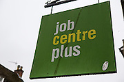A dirty Jobcentre plus sing hanging outside the centre door on the street in Blandford Forum, England, United Kingdom.  Jobcentre Plus is a brand used by the British Government's Department for Work and Pensions for its working-age support service.  It helps unemployed people apply for social security benefit (jobs seekers allowance) and assists them to gain employment.  Jobcentre's have experienced a significant increase in demand for their services during the financial recession and government changes to the welfare system. At the same time they have experienced budget cut backs and many centers have had to close.
