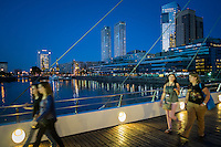 """BUENOS AIRES - CIRCA NOVEMBER 2012: People crossing the """"La Mujer Bridge"""" in the neighborhood of Puerto Madero, circa November 2012. This is a popular tourist destination with over 2.5 million yearly visitors ."""