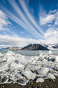 Melting ice on the shore in front of rugged mountains, Royal Bay, South Georgia Island, South Atlantic Ocean