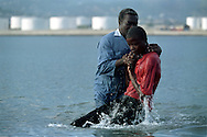 A young man is baptized in a polluted bay in Port-au-Prince, Haiti, May 1995. (Photo by Roger M. Richards)