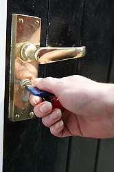 Young woman locking her flat door,