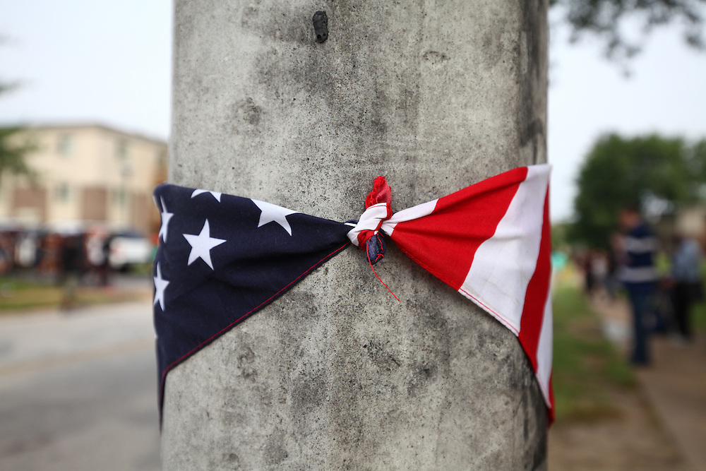 A flag is seen wrapped around a light pole in front of the Mike Brown Jr. memorial on Canfield Dr. Sunday marks the one year anniversary of the death of Mike Brown Jr., killed by Officer Darren Wilson in Ferguson.