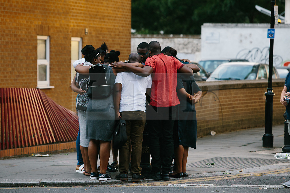 © Licensed to London News Pictures. 16/06/2017. London, UK. A group of local residents hug near the scene of the Grenfell tower block fire in west London. The blaze engulfed the 27-storey building killing 12 - with 34 people still in hospital, 18 of whom are in critical condition. The fire brigade say that they don't expect to find anyone else alive. Photo credit: Radoslaw Dranikowski/LNP