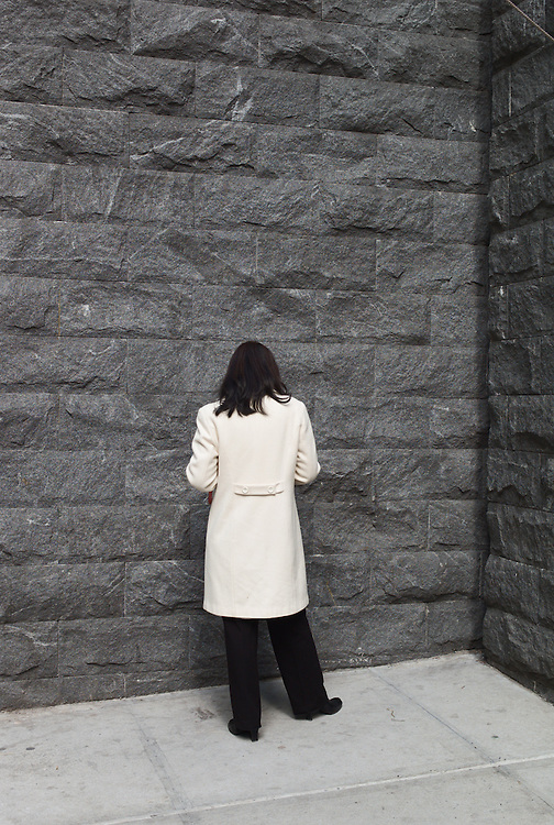 Woman in white coat facing gray stone wall