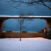 A pedestrian takes shelter along Lake Shore Drive and Lake Michigan as a fresh snow cover the ground.<br />