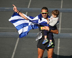 November 13, 2016 - Athens, Greece - Christoforos Merousis holds his child while thanking the stadium after finisthing the Marathon..50.000 long range runners take part in the 42 killometers long Athens Marathon the Authentic in Greece starting from the City of Marathona and ending at Kalimarmaro Stadium in Athens. (Credit Image: © George Panagakis/Pacific Press via ZUMA Wire)