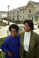 Lois Hinson, and her son Damier Belgrave, 11, left, are shown in their new home in Chatham Estates, Saturday, March 16 2002, in Chester, Pa. Hinson had lived in the old Chester housing projects two years ago, before they were torn down and replaced with new homes. Chatham Estates was built through the U.S. Department of Housing and Urban Development's HOPE VI program, which called for demolishing decrepit public-housing towers and replacing them with townhouses and houses.  (Photo by William Thomas Cain/photodx.com)