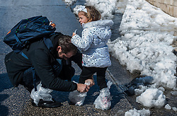 A man helps his daughter to protect her shoes with plastic bags at the snow-covered Western Wall in the Old City of Jerusalem, on Feb. 20, 2015. Some parts of Israel were covered with snow early Friday amid a heavy winter storm and extreme weather conditions. Snow piled up to unusual heights of about 25 cm in Jerusalem, according to a statement by the municipality. Highways to Jerusalem were shut down and residents of the city have been asked not to travel unnecessarily. The municipality said 250 snow ploughs have been operating in order to keep the main roads in the city leading to the major hospitals open. EXPA Pictures © 2015, PhotoCredit: EXPA/ Photoshot/ Li Rui<br /> <br /> *****ATTENTION - for AUT, SLO, CRO, SRB, BIH, MAZ only*****