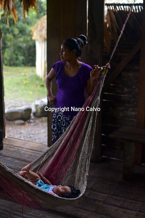 Bribri young mother (Karina) rocking hammock with baby (Simea).<br />