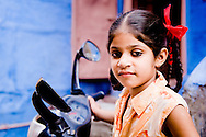 India, Jodhpur. A young girl with red bows posing near a motorbike.