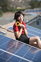 A lady on a solar panalled rooftop holding a sunflower