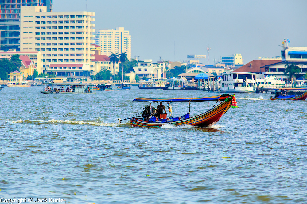 21 NOVEMBER 2012 - BANGKOK, THAILAND:  A long tail boat on the Chao Phraya River. Long tail boats are narrow boats used as taxis on the waterways of Thailand. Bangkok used to be criss crossed by canals and boats were the way people got around. Now most of the canals have been filled in and paved over. The Chao Phraya River, which splits Bangkok, still has regular passenger boat service.   PHOTO BY JACK KURTZ