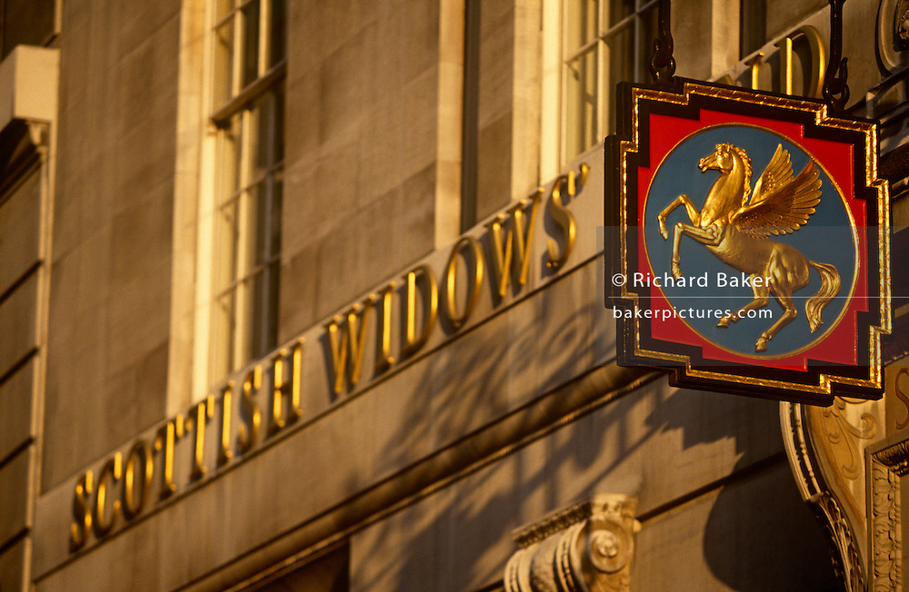 A golden sign hangs outside the Scottish Widows pension institution in Lombard Street in the heart of London's financial heart, the City of London. In bright sunlight, we see the famous Pegasus horse, its wings spread and its legs showing life and vitality. Scottish Widows plc is a life, pensions and investment company located in Edinburgh, Scotland, and is a subsidiary of Lloyds Banking Group. Its product range includes life assurance, pensions, investments and savings. The company has been providing financial services to the UK market since 1815 and is the most trusted life, pensions and investment provider in the UK