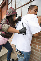 Young woman robbing man with knife