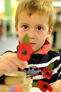 © Licensed to London News Pictures. 07/11/2011. Richmond, UK. Alexander Harding, aged 3,  from Downsend Lodge School, Epsom, shows a red poppy he assembled by himself at the factory's visitor centre. Red Poppies being made in The Poppy Factory in preparation for sale in 2012, Richmond, Surrey today 7th November.  The factory has been supplying the poppy, crosses and wreathes to the British Legion for almost 90 years. It is staffed by veterans, many whom of which are injured, sick or wounded of all ages. Photo credit : Stephen Simpson/LNP