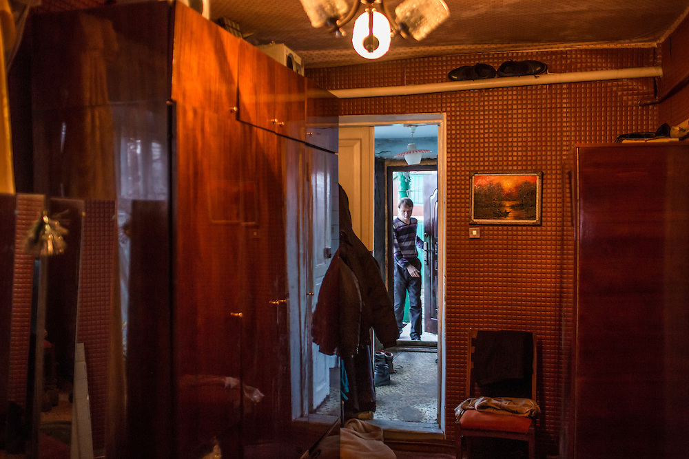 LUHANSK, UKRAINE - MARCH 15, 2015: Aleksandr Kryukov enters the house where he lives with his grandmother in Luhansk, Ukraine. CREDIT: Brendan Hoffman for The New York Times