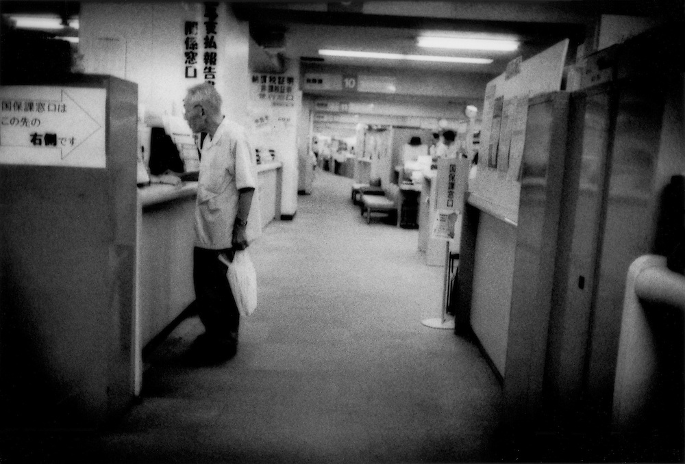 """Poor Record Keeping / Bewildered senior citizen taking care of his insurance issues in a corridor lined with file cabinets in the digital age at a Tokyo """"kuyakusho"""" or ward office, the same office that is responsible for maintaining each family's """"koseki tohon"""" (family registry).  The Byzantine bureaucracy at this """"kuyakusho"""", or ward office,  is typical of government offices nationwide where families have registered births and deaths for centuries in a system adopted from China called the """"koseki tohon"""", Tokyo, Japan.  According to NHK, the government television network, a 186 year old was registered as living in Yamanashi Prefecture and that was a record until a 200 year old was found registered as still alive in August 2010.  Numbers have fluctuated wildly with a 6 September Yomiuri Shimbun (Newspaper) article claiming 241 missing centenarians.  Then a 15 September Kyodo News article claimed that a """"survey was conducted after a separate, family-based registry system indicated tens of thousands of centenarians are """"missing"""" despite being registered as alive""""."""