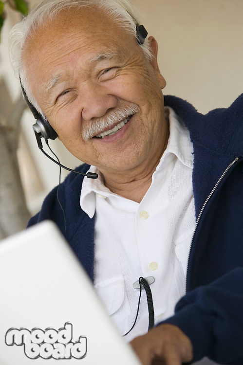 Man Using Headset and Laptop