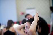A contestant for the Miss Universe China Pageant  adjusts her hair as she practices proper make application at a training camp for contestants in Beijing, China on Thursday, June 23, 2011.   The training camp was created by cosmetics businesswoman and Chinese-American television personality Yue-Sai Kan's to give China, which has never won a Ms. Universe Contest, a cpotential contender in the upcoming beauty pagent.
