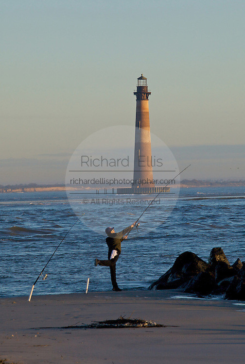 Sunrise over Folly Beach with an early morning fisherman and Morris Lighthouse near Charleston, SC. Morris Lighthouse dates back to 1767 but was rebuilt in the current form in 1873 after it was destroyed in the civil war.