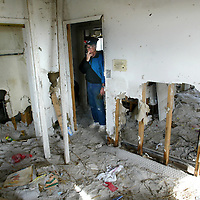 Thomas Brandon,65, a retired navy pilot, looks at the damage in a guest bedroom of the home he has lived in for 34 years on Pensacola Beach on Wednesday January 5, 2005. Almost 4 months after Hurricane Ivan devasted the area, Brandon's home is still filled with sand, trees and other debris. Brandon has been living in a FEMA trailer in front of his home. Brandon is currently deciding if it is better to renovate or rebuild his home.