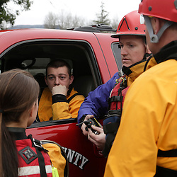 Members of a swift water rescue team monitor radio traffic after a large mudslide blocked Highway 530 near Oso, Washington March 22, 2014. Three people died and at least eight others were injured on Saturday in a landslide that destroyed six or more homes along a state highway in northwest Washington state, officials said. REUTERS/Jason Redmond (UNITED STATES)