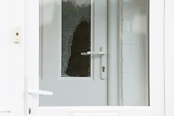 © Licensed to London News Pictures . 17/01/2015 . Stockport , UK . Smashed front door glass at 28 Meadway Road , Cheadle Hulme , Stockport this afternoon (Saturday 17th January 2015 ) after a woman and a man - named as magistrate Yvonne Davies and her husband Andrew - were found dead inside after an apparent murder-suicide last night (16th January 2015) .  A neighbour described hearing a commotion and seeing a man smash the front door with a hammer to gain entry . Photo credit : Joel Goodman/LNP