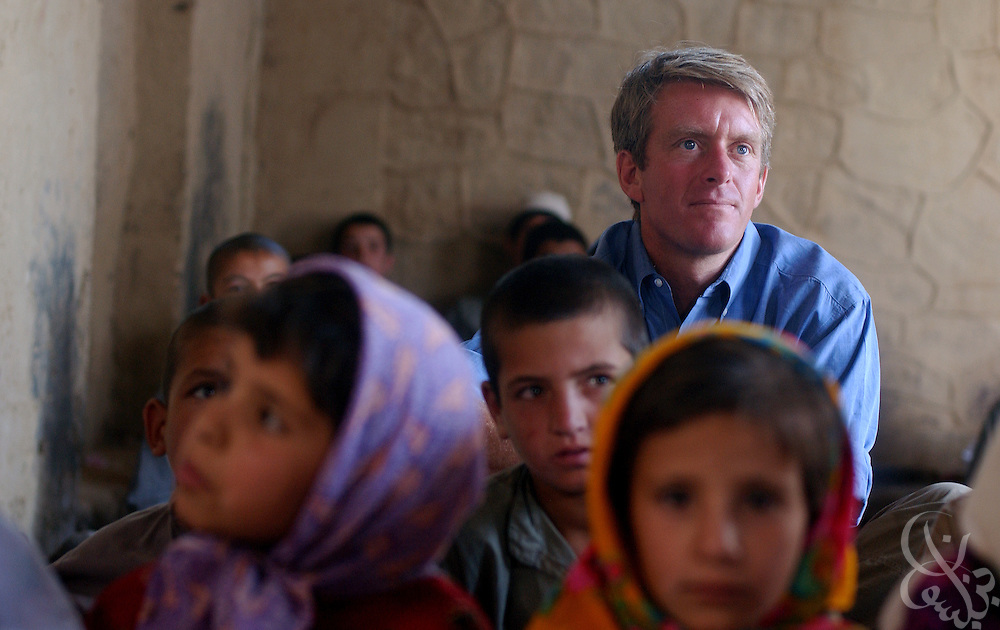CNN correspondent Nick Robertson sits among a group of Afghan orphans during a visit by U.S. military civil affairs personnel July 10, 2002 at the Charikar Childrens Orphanage in Charikar, Afghanistan. A CNN crew accompanied the civil affairs personnel as they handed out school supplies, toys, and candy to nearly 100 young Afghan boys and girls who live at the orphanage, which is located near the Bagram Airbase.