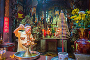11 APRIL 2012 - HO CHI MINH CITY, VIETNAM:  A man pours oil over a diety at the Jade Emperor Pagoda in Ho Chi Minh City, Vietnam. It was built in 1909 by a Cantonese (Quang Dong) Congregation. It is one of the most colourful pagodas in HCMC, filled with statues of phantasmal divinities and grotesque heroes. Smoke of burning joss sticks fills the air, obscuring the exquisite woodcarvings decorated with gilded Chinese characters. The roof is covered with elaborate tile work, while the statues, which represent characters from both the Buddhist and Taoist traditions, are made of reinforced papier-mâché. The pagoda is dedicated to the Emperor of Jade, the supreme Taoist god. Ho Chi Minh City, formerly Saigon, is the largest city in Vietnam and the country's commercial center. It was the capital of South Vietnam before the reunification in 1975 and still shows more signs of American influence than northern Vietnam does.    PHOTO BY JACK KURTZ