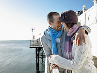 Couple laughing standing on pier half length