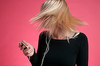 Young woman holding mp3 player and tossing hair