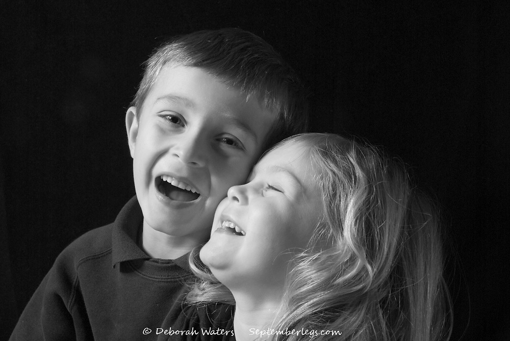 Black and white portait of young bother and sister laughing, isolated on black