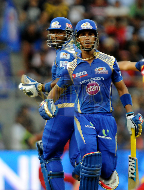 Kieron Pollard of Mumbai Indians and Lendl simmons of Mumbai Indians run between the wickets during match 46 of the Pepsi IPL 2015 (Indian Premier League) between The Mumbai Indians and The Royal Challengers Bangalore held at the Wankhede Stadium in Mumbai, India on the 10th May 2015.<br /> <br /> Photo by:  Pal Pillai / SPORTZPICS / IPL