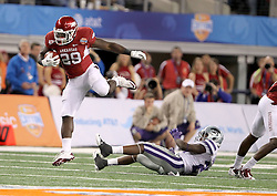 Arkansas running back Broderick Green (29) hurdles over a player and gets a big play to help put the game away before being tackled by Kansas State defensive back Matthew Pearson (38) during the 2012 AT&T Cotton Bowl game at Cowboy Stadium in Arlington, Tx on Jan 6th, 2012 .