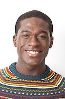Portrait of happy young African American man in knitwear against white background